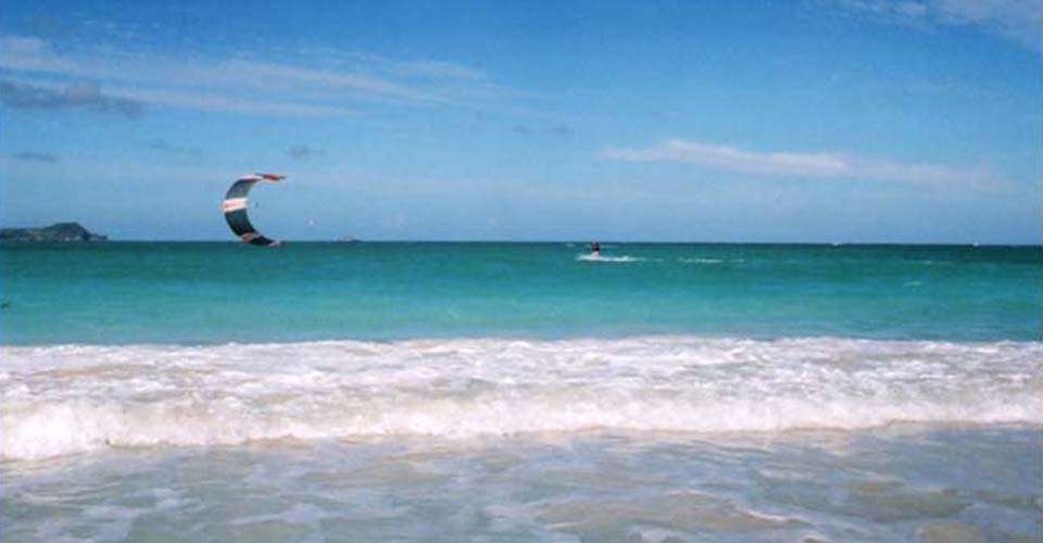 A kite surfer sails across the surf off Kailua Beach.